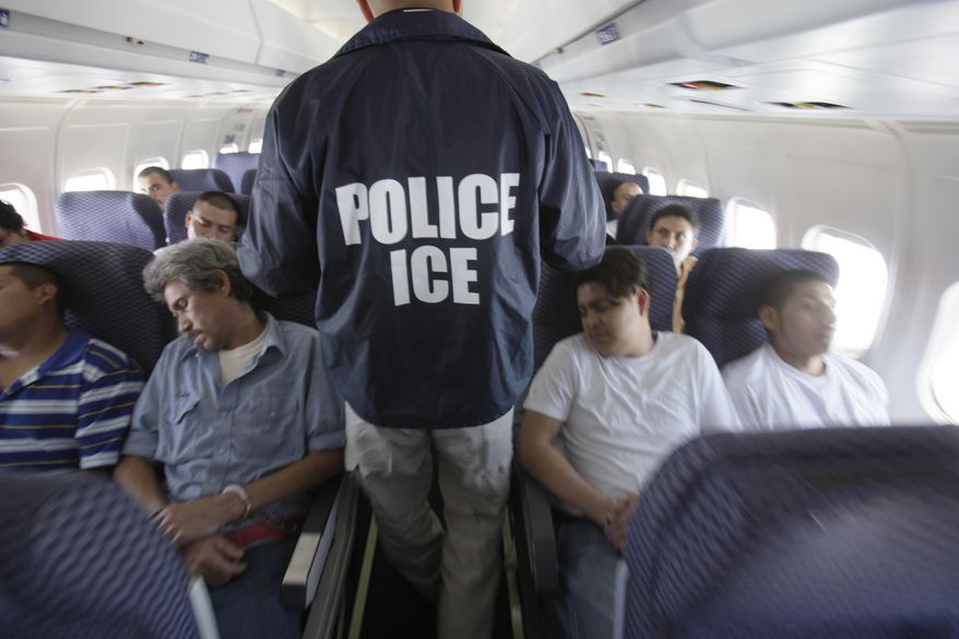 In this May 25, 2010 file photo, an Immigration and Customs Enforcement agent walks down the aisle among shackled Mexican immigrants a boarded a U.S. Immigration and Customs Enforcement charter jet for deportation in the air between Chicago, Il. and Harlingen, Texas. A Homeland Security Department internal watchdog says U.S. Immigration and Customs Enforcement could have saved millions of dollars on charter flights carrying deported immigrants to their home countries by not leaving seats empty. (AP Photo/LM Otero, File)