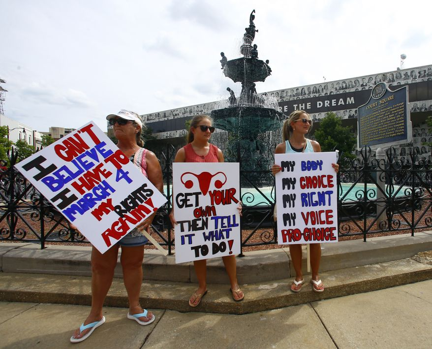 Women hold signs as they gather to march to the Capitol for women's rights, Sunday, May 19, 2019, in Montgomery, Ala. (AP Photo/Butch Dill)