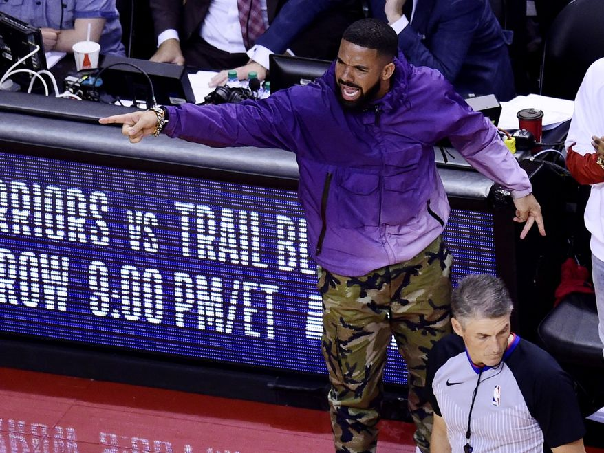 Recording artist Drake points on the sideline during the second half of Game 3 of the NBA basketball playoffs Eastern Conference finals between the Milwaukee Bucks and the Toronto Raptors in Toronto, Sunday, May 19, 2019. (Frank Gunn/The Canadian Press via AP)