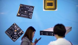 FILE - In this May 18, 2018, file photo, visitors walk past a display showing microchips and circuit boards at the 21st China Beijing International High-tech Expo in Beijing. For four decades, Beijing has cajoled or pressured foreign companies to hand over technology. And its trading partners say if that didn't work, China stole what it wanted. (AP Photo/Mark Schiefelbein, File)