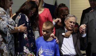 Texas Gov. Greg Abbott, right, holds hands with survivors during a dedication ceremony for a new sanctuary and memorial room at the First Baptist Church in Sutherland Springs, Texas, Sunday, May 19, 2019. In 2017 a gunman opened fire at the church and killed more than two dozen congregants. (AP Photo/Eric Gay)