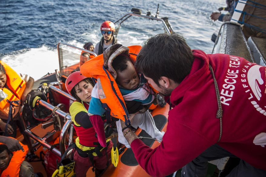 A baby is loaded into the rescue vessel of the Spanish NGO Proactiva Open Arms, after being rescued in the Central Mediterranean Sea at 45 miles from Al Khums, Libya. (AP Photo/Olmo Calvo, File)