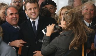 French President Emmanuel Macron poses for photos with supporters in Biarritz, southwestern France, Friday, May 17, 2019. (AP Photo/Bob Edme)