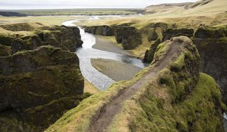 """This photo taken Wednesday, May 1, 2019, shows a cliff at the Fjadrárgljúfur canyon in southeastern Iceland. The canyon area has suffered environmental damages after intense traffic, prompted by the music video """"I'll Show You"""" by Justin Bieber. (AP Photo/Egill Bjarnason)"""