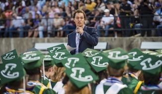 Actor and 1988 Longview High School graduate Matthew McConaughey delivers the commencement speech at the school's graduation ceremony in Longview, Texas, on Friday, May 17, 2019. McConaughey has finally received his high school diploma, more than 30 years after graduating. (Les Hassell/The News-Journal via AP)