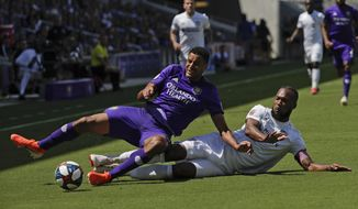 Orlando City's Tesho Akindele, left, and FC Cincinnati's Kendall Waston battle for possession of the ball during the first half of an MLS soccer match, Sunday, May 19, 2019, in Orlando, Fla. (AP Photo/John Raoux)