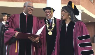 Robert F. Smith, left, laughs with David Thomas, center, and actress Angela Bassett at Morehouse College on Sunday, May 19, 2019, in Atlanta. Smith, a billionaire technology investor and philanthropist, said he will provide grants to wipe out the student debt of the entire graduating class at Morehouse College - an estimated $40 million. Smith, this year's commencement speaker, made the announcement Sunday morning while addressing nearly 400 graduating seniors of the all-male historically black college in Atlanta.  (Bo Emerson/Atlanta Journal-Constitution via AP)