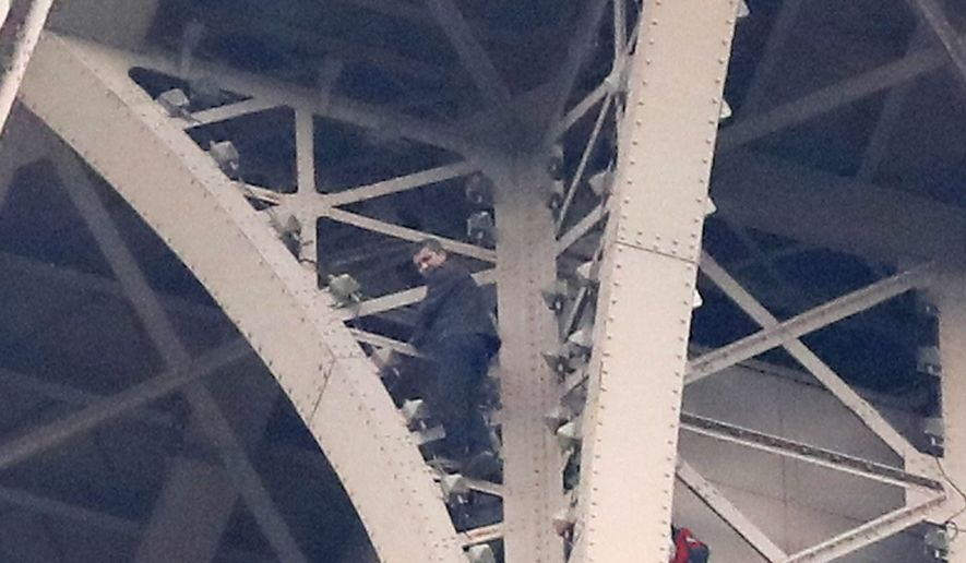 A climber is pictured between two iron columns of the Eiffel Tower while a rescue worker is partially seen at right, Monday, May 20, 2019 in Paris. The Eiffel Tower has been closed to visitors after the man has tried to scale it. (AP Photo/Michel Euler)