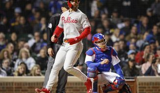Philadelphia Phillies' Bryce Harper, left, scores on a triple by Cesar Hernandez against the Chicago Cubs during the sixth inning of a baseball game, Monday, May 20, 2019, in Chicago. (AP Photo/Kamil Krzaczynski)