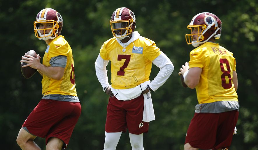 Washington Redskins quarterback Dwayne Haskins Jr., center, watches as quarterbacks Josh Woodrum, left, and Case Keenum run a drill during a practice at the team's NFL football practice facility, Monday, May 20, 2019, in Ashburn, Va. (AP Photo/Patrick Semansky) ** FILE **