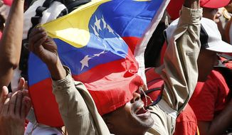 A supporter of Venezuela's President Nicolas Maduro shouts his support for him outside Miraflores presidential palace in Caracas, Venezuela, Monday, May 20, 2109. Maduro is celebrating the anniversary of his disputed re-election amid a growing humanitarian crisis and political upheaval. (AP Photo/Ariana Cubillos)