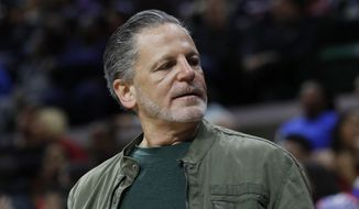 """FILE- In an Oct. 12, 2018 file photo, Quicken Loans and Rock Ventures founder Dan Gilbert is seen during a basketball game in East Lansing, Mich. Gilbert is starting a ballot drive as a """"failsafe"""" in case Michigan's Republican-led Legislature and Democratic Gov. Gretchen Whitmer don't enact legislation to cut the country's highest auto insurance premiums. Quicken Loans vice president of government affairs Jared Fleisher said Monday that a ballot committee, Citizens for Lower Auto Insurance Rates, will be created this week. (AP Photo/Carlos Osorio, File)"""