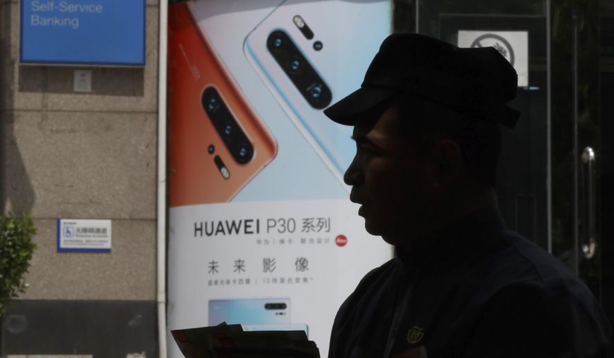 In this photo taken Thursday, May 16, 2019, a man handing out pamphlets is silhouetted against a advertisement for the latest smartphones from Huawei in Beijing. Google is assuring users of Huawei smartphones the American company's services still will work on them following U.S. government restrictions on doing business with the Chinese tech giant. (AP Photo/Ng Han Guan)
