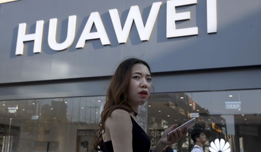 A woman uses a smartphone outside a Huawei store in Beijing Monday, May 20, 2019. Google is assuring users of Huawei smartphones the American company's services still will work on them following U.S. government restrictions on doing business with the Chinese tech giant. (AP Photo/Ng Han Guan)