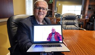 In this Wednesday, May 8, 2019, photo, Allen Henderson, General Manager of HIS Radio Station in Greenville, S.C., speaks via Skype to his brother Andre Gantois who is in France. Henderson took a DNA test on a whim, because the company had a special offer on its prices and learned he had a half-brother in France. (AP Photo/Richard Shiro)