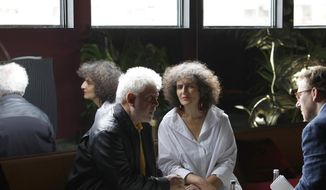 Intepreter Massoumeh Lahidji, centre, translates an interview with director Pedro Almodovar, left, and Associated Press film writer Jake Coyle, right at the 72nd international film festival, Cannes, southern France, Sunday, May 19, 2019. (AP Photo/Petros Giannakouris)
