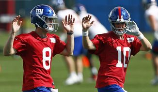 New York Giants quarterbacks Eli Manning (10) and Daniel Jones (8) warm up during an NFL football practice Monday, May 20, 2019, in East Rutherford, N.J. (AP Photo/Adam Hunger) ** FILE **