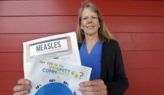 "In this photo taken Wednesday, May 15, 2019, Vashon Island High School nurse Sarah Day holds information about measles vaccinations as she poses for a photo in Vashon Island, Wash. Since Day began communal living on Vashon Island more than 20 years ago, the registered nurse has been advocating for getting kids their shots against a loud contingent of anti-vaccine parents in the close-knit community of about 11,000 that's accessible only by ferry, a serene 20-minute ride from Seattle. And it may now be working, thanks to a ""perfect storm"" of changes being felt on the island, Day said. (AP Photo/Elaine Thompson)"