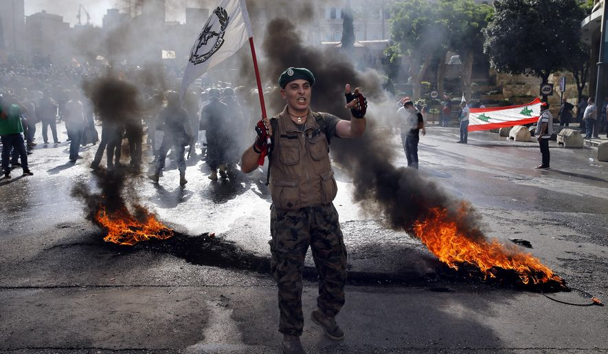 """A retired Lebanese soldier chants slogans while holding an army flag, during a protest in Beirut, Lebanon, Monday, May 20, 2019, as the government faces a looming fiscal crisis. Over one hundred protesters gathered Monday in downtown Beirut shouting """"Thieves, thieves!"""" as the Cabinet met for its 16th session to reach agreement on controversial budget cuts. (AP Photo/Bilal Hussein)"""