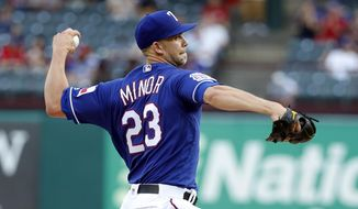Texas Rangers starting pitcher Mike Minor (23) throws to the Seattle Mariners in the first inning of a baseball game in Arlington, Texas, Monday, May 20, 2019. (AP Photo/Tony Gutierrez)