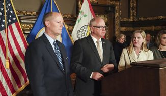 Gov. Tim Walz, center, with Senate Majority Leader Paul Gazelka, left, and House Speaker Melissa Hortman, listens at a news conference to announce a budget deal in St. Paul, Minn., Sunday, May 19, 2019. Walz and top legislative leaders reached a bipartisan budget deal Sunday in which the governor dropped his proposed gas tax increase but got to keep most of an expiring tax that helps fund health care programs, Republicans got an income tax cut for middle-class Minnesotans and both sides claimed credit for additional spending on education. (Glen Stubbe/Star Tribune via AP)