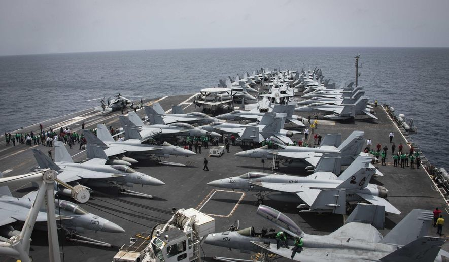 In this Sunday, May 19, 2019, photo released by the U.S. Navy, sailors partake in a foreign object and debris walk-down on the flight deck of the Nimitz-class aircraft carrier USS Abraham Lincoln. (Mass Communication Specialist 3rd Class Garrett LaBarge/U.S. Navy via AP)
