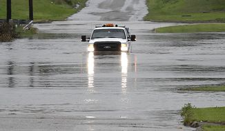 """A pickup truck drives on a flooded street in Enid, Okla., Monday, May 20, 2019. An intense storm system that weather forecasters labeled """"particularly dangerous"""" swept through the Southern Plains Monday, spawning a few tornadoes that caused some damage and a deluge of rain but no reports of injuries. (Billy Hefton/The Enid News & Eagle via AP)"""