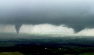 """This image made from video provided by KWTV-KOTV shows two funnel clouds formed in Crescent, Okla., Monday, May 20, 2019. An intense storm system that weather forecasters labeled """"particularly dangerous"""" swept through the Southern Plains Monday, spawning a few tornadoes that caused some damage and a deluge of rain but no reports of injuries. (KWTV-KOTV via AP)"""