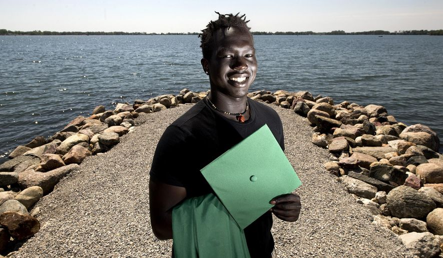 In a Wednesday, May 15, 2019 photo, Cham Deng, a graduating senior at Storm Lake High is shown in Chautauqua Park in Storm Lake, Iowa. Deng, born in the Minneapolis area to immigrants from Sudan, will graduate in ceremonies Sunday, May 26, 2019 and attend Iowa Central Community College to study accounting and play basketball.  (Tim Hynds/Sioux City Journal via AP)=
