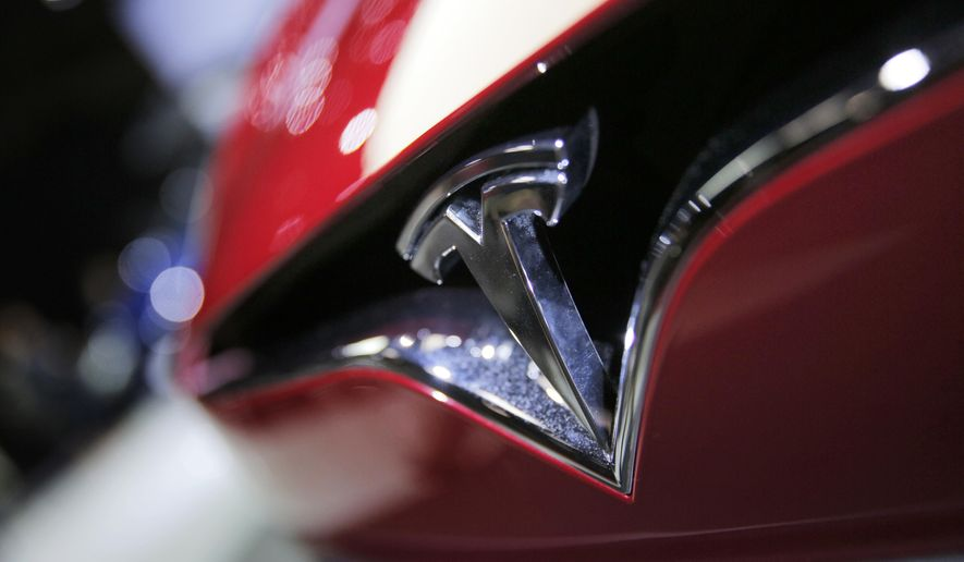 FILE- This Sept. 30, 2016, file photo shows the logo of the Tesla model S at the Paris Auto Show in Paris, France. Shares of Tesla are down 50 percent since September 2019, with concerns about Model 3 demand in the U.S. at the forefront. Daniel Ives of WedBush said in a client note Monday, May 20 that so far there seems to be mixed signals on Model 3 demand, which could make it harder for Tesla to achieve a profit in its third and fourth quarters and the future. (AP Photo/Christophe Ena, File)