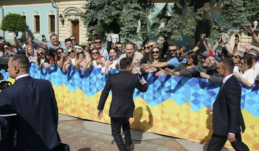 Ukrainian President-elect Volodymyr Zelenskiy greeds his supporters before inauguration ceremony in Kiev, Ukraine, Monday, May 20, 2019. Zelenskiy overwhelming won the presidential election last month, beating incumbent Petro Poroshenko. (AP Photo/Efrem Lukatsky)