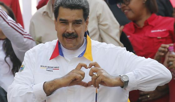 Venezuela's President Nicolas Maduro gestures a heart symbol to supporters outside Miraflores presidential palace in Caracas, Venezuela, Monday, May 20, 2109. Maduro is celebrating the anniversary of his disputed re-election amid a growing humanitarian crisis and political upheaval. (AP Photo/Ariana Cubillos)