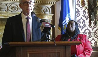 Wisconsin Gov. Tony Evers refuses to address comments his spokeswoman made over the weekend accusing Republican legislative leaders of being sexist on Monday, May 20, 2019, in Madison, Wis. Democratic state Rep. Sheila Stubbs listens to Evers, who said he would only comment on an automatic voting registration bill being unveiled. (AP Photo/Scott Bauer)