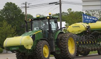 """A farmer drives a tractor with a """"Trump, Keep America Great,"""" flag, Tuesday, May 21, 2019, in Warrenton, Mo. Trump won the presidency by winning rural America, in part by pledging to use his business savvy and tough negotiating skills to take on China and put an end to trade practices that have hurt farmers for years. (AP Photo/Wilfredo Lee)  **FILE**"""