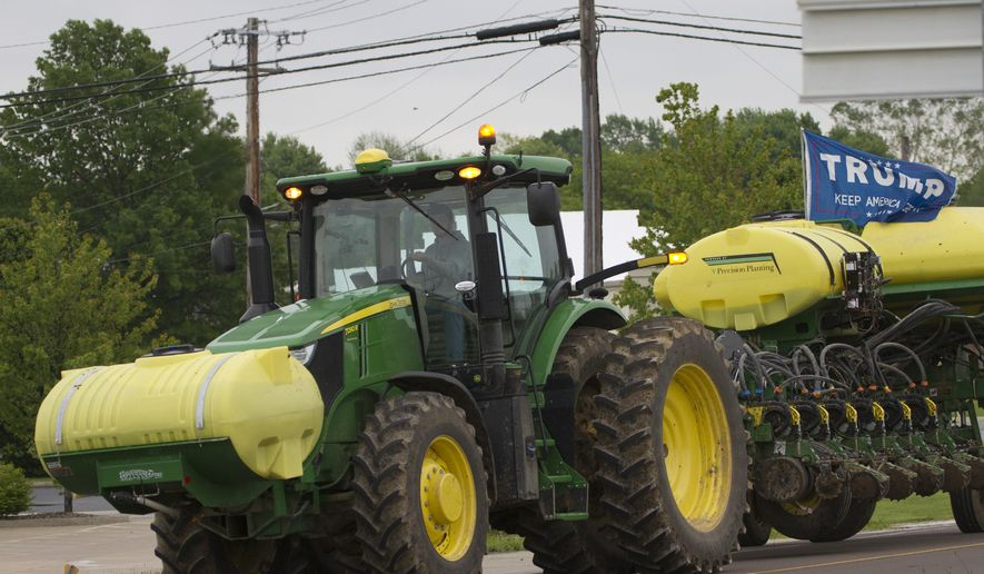 """A farmer drives a tractor with a """"Trump, Keep America Great,"""" flag, Tuesday, May 21, 2019, in Warrenton, Mo. Trump won the presidency by winning rural America, in part by pledging to use his business savvy and tough negotiating skills to take on China and put an end to trade practices that have hurt farmers for years. (AP Photo/Wilfredo Lee)"""