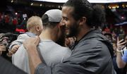 Former NFL football quarterback Colin Kaepernick, right, hugs Golden State Warriors guard Stephen Curry as Curry holds his son Canon, after Game 4 of the NBA basketball playoffs Western Conference finals against the Portland Trail Blazers, Monday, May 20, 2019, in Portland, Ore. The Warriors won 119-117 in overtime. (AP Photo/Ted S. Warren)