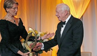 FILE - In this Jan. 27, 2017, file photo, former President Jimmy Carter, right, accepts the O'Connor Justice Prize from former U.S. Ambassador to Finland Barbara Barrett, left, at The Sandra Day O'Connor College of Law at Arizona State University Justice Prize Dinner in Phoenix. President Donald Trump has nominated Barrett to be the next secretary of the Air Force. (AP Photo/Ross D. Franklin, File)