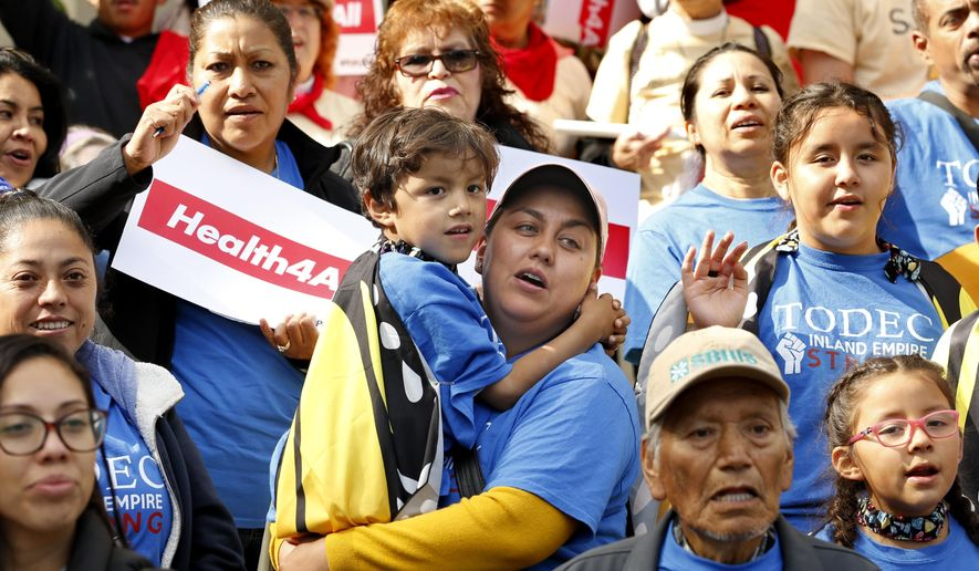 Oralia Sandoval, center, holds her son Benjamin, 6, as she participates in an Immigrants Day of Action rally, Monday, May 20, 2019, in Sacramento, Calif. Gov. Gavin Newsom has proposed offering government-funded health care benefits to immigrant adults ages 19 to 25 who are living in the country illegally. State Sen. Maria Elena Durazo, D-Los Angeles, has proposed a bill to expand that further to include seniors age 65 and older. (AP Photo/Rich Pedroncelli) ** FILE **