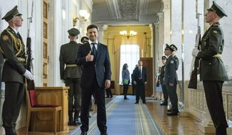 Ukrainian President-elect Volodymyr Zelenskiy, center, gestures as he waits to attend his inauguration ceremony in Kiev, Ukraine, Monday, May 20, 2019. Ukrainian TV star Volodymyr Zelenskiy has sought to capitalize on his huge popularity, dissolving the country's parliament Monday minutes after he was sworn in as president. (AP Photo/Zoya Shu, Pool)