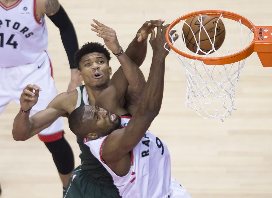 Toronto Raptors center Serge Ibaka battles for the ball against Milwaukee Bucks forward Giannis Antetokounmpo during the second half of Game 4 of the NBA basketball playoffs Eastern Conference finals, Tuesday, May 21, 2019, in Toronto. (Nathan Denette/The Canadian Press via AP) **FILE**
