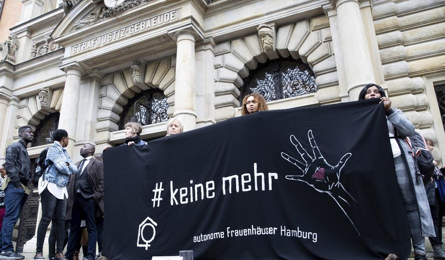 """Representatives of a women's shelter in Hamburg stand at a vigil for a woman killed with a banner with the inscription """"# keine mehr"""" in front of the criminal justice building in Hamburg, Germany, Tuesday, May 21, 2019. Almost six months after the deadly stabbing of a mother of four in Hamburg's Altona-Nord district, a trial against her husband began on Tuesday. In December 2018, the 50-year-old defendant is said to have used a knife to inflict 50 stab wounds and cuts on his wife, who lives separately from him, in her apartment.  (Christian Charisius/dpa via AP)"""