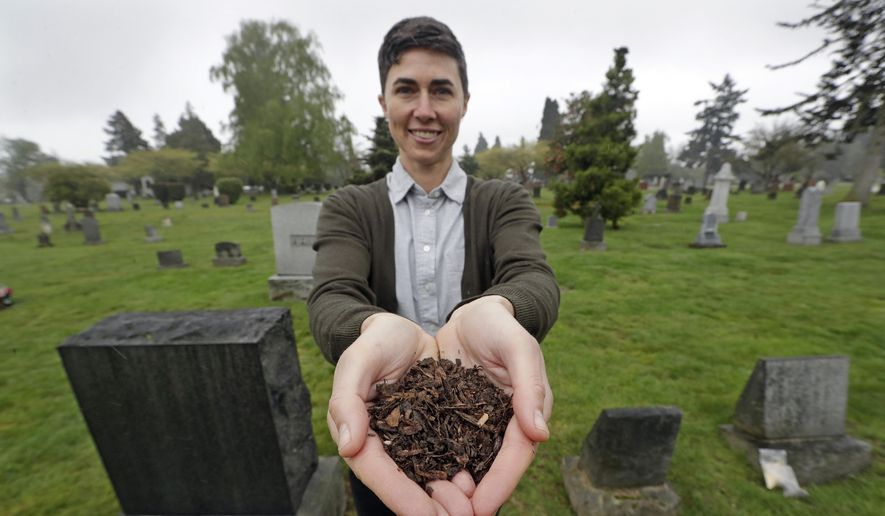 """In this April 19, 2019, file photo, Katrina Spade, the founder and CEO of Recompose, a company that hopes to use composting as an alternative to burying or cremating human remains, poses for a photo in a cemetery in Seattle, as she displays a sample of compost material left from the decomposition of a cow using a combination of wood chips, alfalfa and straw. On Tuesday, May 21, 2019, Washington Gov. Jay Inslee signed a bill into law that allows licensed facilities to offer """"natural organic reduction,"""" which turns a body, mixed with substances such as wood chips and straw, into soil in a span of several weeks. Th law makes Washington the first state in the U.S. to approve composting as an alternative to burying or cremating human remains. (AP Photo/Elaine Thompson, File) **FILE**"""