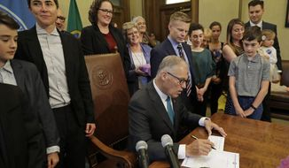 "Katrina Spade, upper left, the founder and CEO of Recompose, a company that hopes to use composting as an alternative to burying or cremating human remains, looks on Tuesday, May 21, 2019, as Washington Gov. Jay Inslee, center, signs a bill into law at the Capitol in Olympia, Wash., that allows licensed facilities to offer ""natural organic reduction,"" which turns a body, mixed with substances such as wood chips and straw, into soil in a span of several weeks. The law makes Washington the first state in the U.S. to approve composting as an alternative to burying or cremating human remains. (AP Photo/Ted S. Warren)"