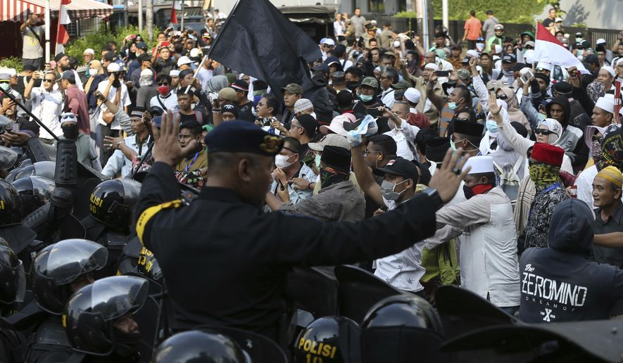 Indonesian police officers block supporters of Indonesian presidential candidate Prabowo Subianto during a rally outside the Elections Supervisory Agency (Bawaslu) building in Jakarta, Indonesia, Tuesday, May 21, 2019. Indonesia's President Joko Widodo has been elected for a second term, official results showed Tuesday, in a victory over a would-be strongman who aligned himself with Islamic hardliners. (AP Photo/Achmad Ibrahim)