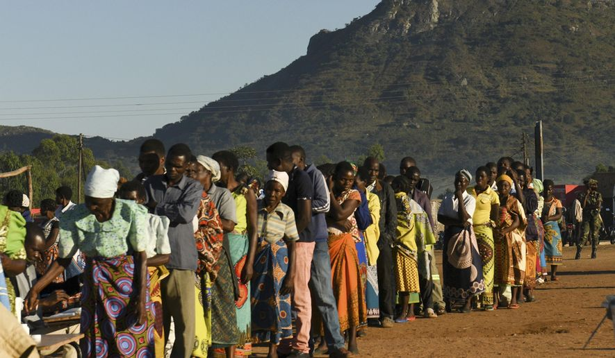 People queue to cast their votes near Blantyre, Malawi, Tuesday, May 21, 2019. Voting is underway to elect a new president in which 78-year-old President Peter Mutharika is seeking re-election to a second term. (AP Photo/Thoko Chikondi)