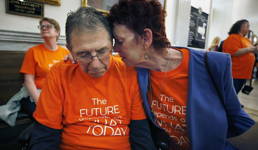 Mary Ann DeMello hugs her husband Frank, who has Alzheimer's disease, during a rally at the Statehouse in Boston, Tuesday, May 21, 2019. Advocates gathered as the Massachusetts Senate began debating its version of a proposed $42.7 billion state budget. (AP Photo/Michael Dwyer)