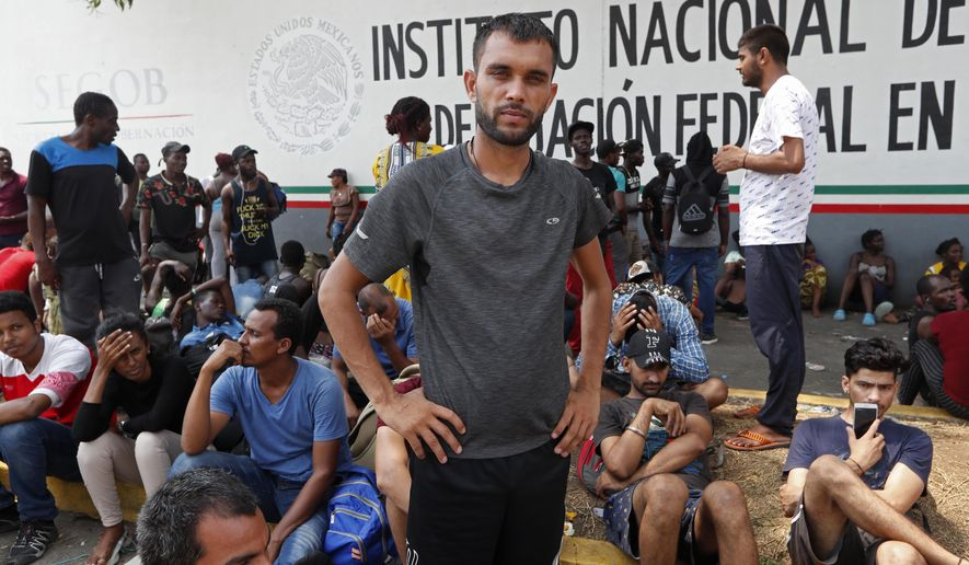 FILE - In this April 29, 2019 file photo, Rahjit, from India, poses for a photo as he waits with other migrants for a ticket to register their entry into Mexico at an immigration station in Tapachula, Chiapas state, Mexico. The National Immigration Institute said on Monday, May 20, 2019, it is studying a change in the way it handles the migrants who have been overwhelming its facilities near the border with Guatemala. (AP Photo/Moises Castillo, File)