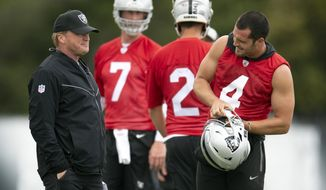 Oakland Raiders head coach Jon Gruen, left, confers with his quarterbacks Mike Glennon (7), Landry Jones (2) and Derek Carr (4) during an NFL football official team activity, Tuesday, May 21, 2019, at team headquarters in Alameda, Calif. (AP Photo/D. Ross Cameron)