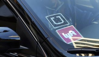 In this Jan. 12, 2016, file photo, a rideshare car displays Lyft and Uber stickers on its front windshield in downtown Los Angeles.  (AP Photo/Richard Vogel, File) **FILE**