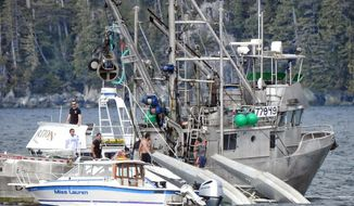 This Monday, May 20, 2019 photo provided by Aerial Leask shows good Samaritans off of fishing vessels attempting to bring in a floatplane that crashed in the harbor of Metlakatla, Alaska. Officials said the pilot and passenger aboard the plane died, and the National Transportation Safety Board is investigating the crash. (Aerial Leask via AP)